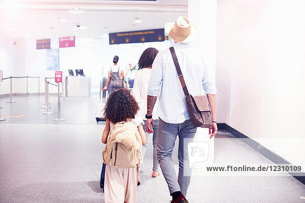 Familie auf dem Weg zur Abflughalle am Flughafen  Rückansicht