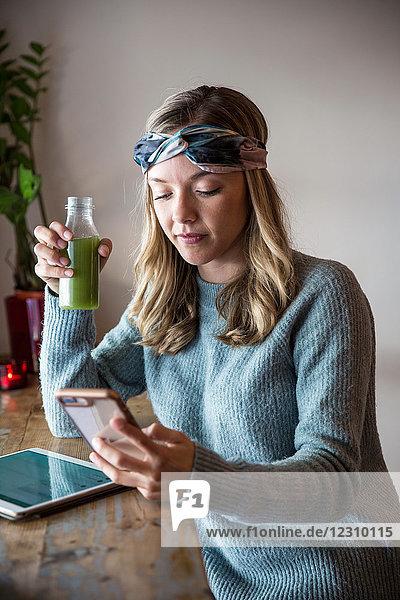 Junge Frau mit Gemüsesaft betrachtet Smartphone am Fensterplatz eines Cafés