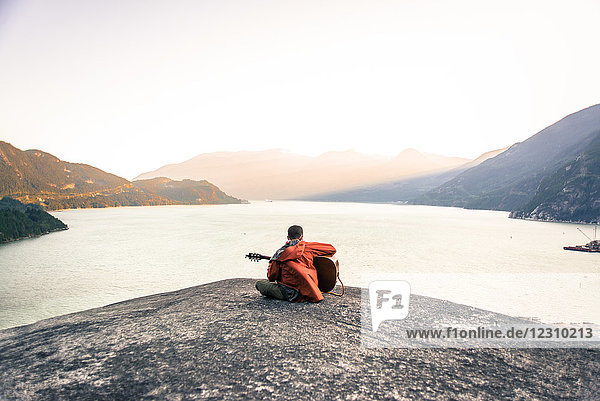 Young man sitting on The Malamute  playing guitar  rear view  Squamish  Canada