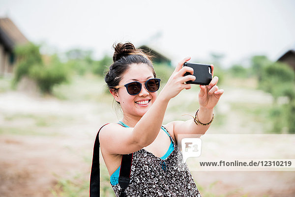 Young female tourist taking smartphone selfie  Botswana  Africa