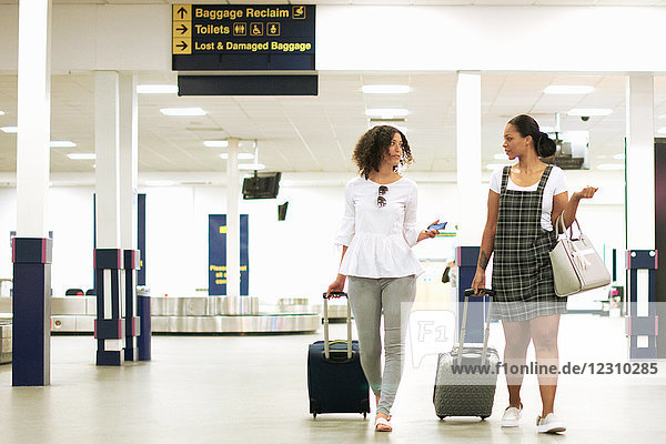 Freunde mit Rollkoffern auf dem Flughafen