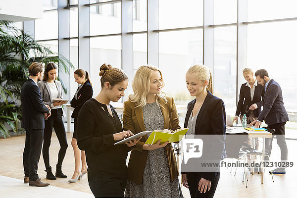 Geschäftsfrauen im Büro-Atrium mit digitalem Tablet