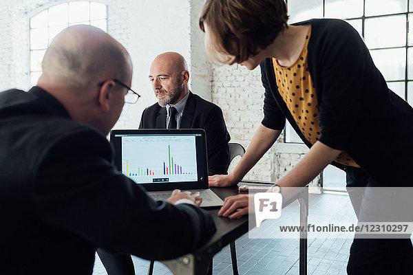 Kollegen betrachten grafische Daten auf Laptop