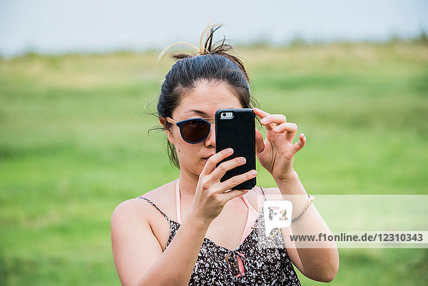 Junge Touristin fotografiert mit Smartphone  Botswana  Afrika