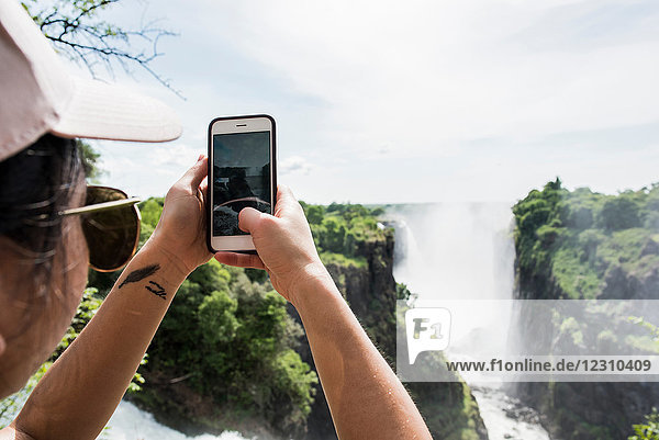 Young female tourist taking smartphone photographs of Victoria Falls  over shoulder view  Zimbabwe  Africa