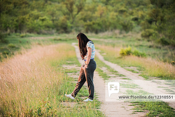 Young female tourist on dirt track in Kruger National Park  over shoulder view  South Africa