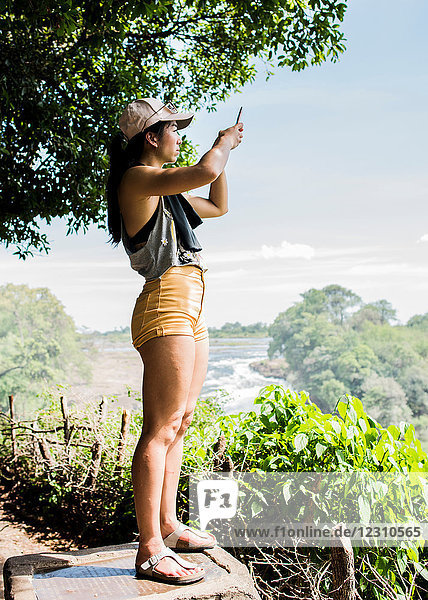 Young female tourist taking smartphone photographs of Victoria Falls  Zimbabwe  Africa