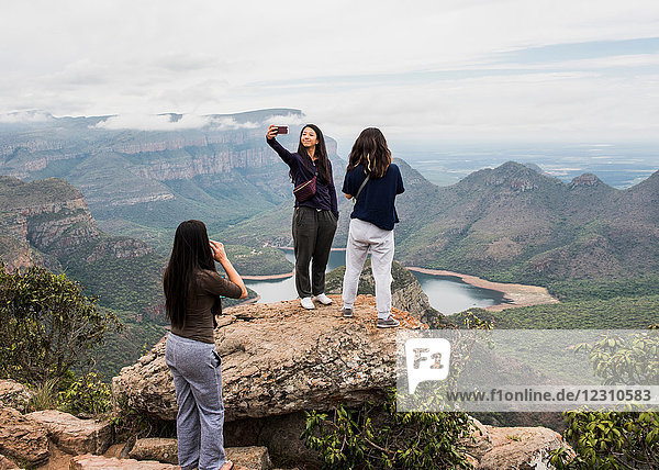 Three young female tourists looking out and taking selfie from The Three Rondavels  Mpumalanga  South Africa
