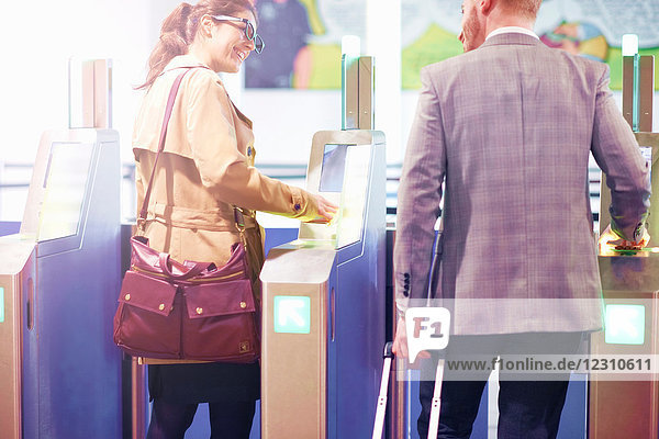 Businessman and woman walking through security gate at airport  rear view