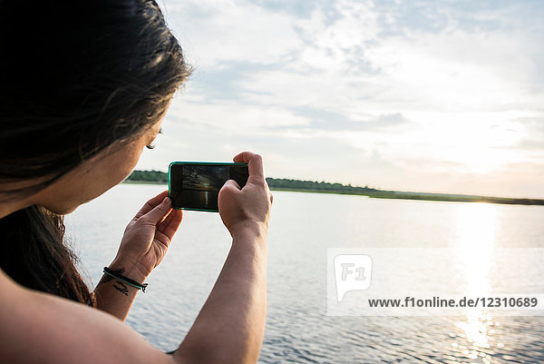 Young female tourist photographing sunset on Chobe River  Botswana  Africa