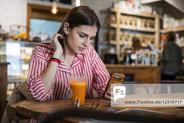 Junge Frau sitzt im Cafe  benutzt Smartphone  Smoothie auf dem Tisch vor ihr