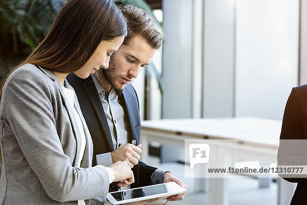 Junge Geschäftsfrau und Mann im Büro schauen auf digitales Tablet