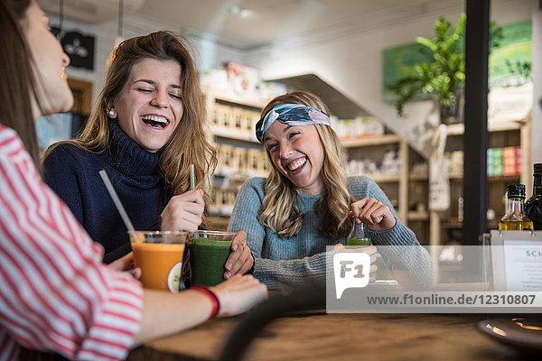 Drei Freundinnen  sitzen im Café  trinken Smoothies  lachen