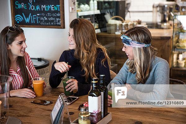 Drei junge Freundinnen mit Gemüsesaft beim Plaudern im Café