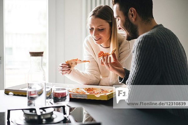 Couple eating takeaway pizza
