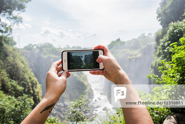 Young female tourist taking smartphone photographs of Victoria Falls  detail of hands  Zimbabwe  Africa