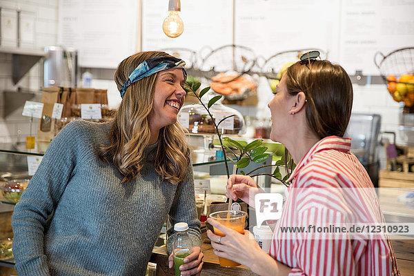 Zwei junge Freundinnen lachen zusammen in einem Café