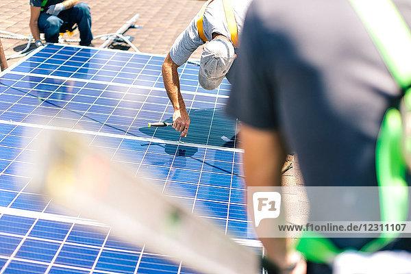 Drei Handwerker installieren Sonnenkollektoren auf dem Hausdach Drei Handwerker installieren Sonnenkollektoren auf dem Hausdach