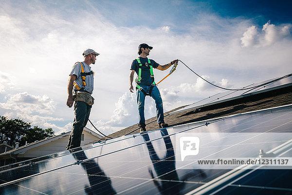 Zwei Handwerker installieren Sonnenkollektoren auf dem Hausdach  Blickwinkel gering