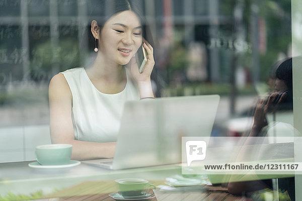 Geschäftsfrau sitzt im Café  benutzt Smartphone und Laptop  durch Fenster gesehen