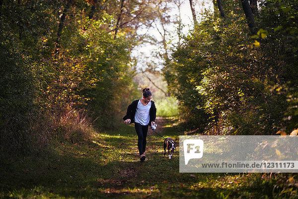 Junges Mädchen beim Hundeausführen in ländlicher Umgebung