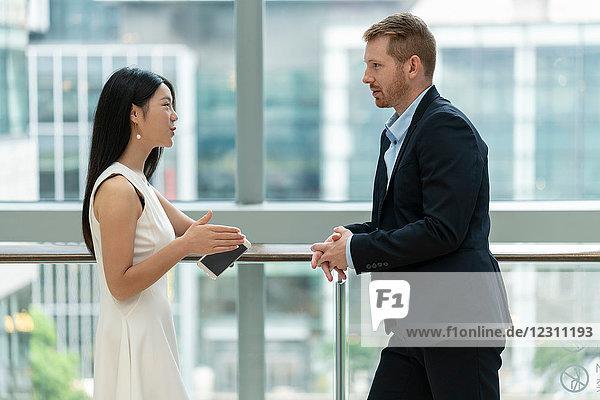Geschäftsmann und Geschäftsfrau stehen am Fenster  im Gespräch