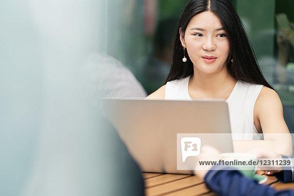 Gruppe von Geschäftsleuten  die sich im Café treffen  mit Laptop