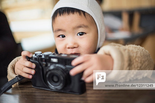 Little boy holding camera on table