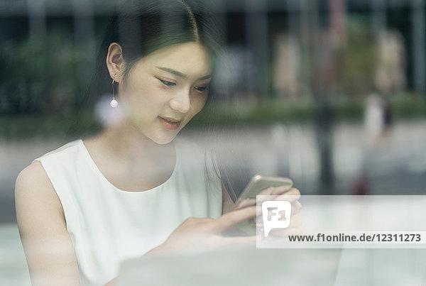 Geschäftsfrau mit Smartphone und Laptop  durch Fenster betrachtet