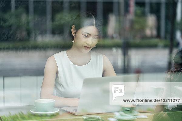 Geschäftsfrau sitzt im Cafe  benutzt Laptop  durch Fenster gesehen