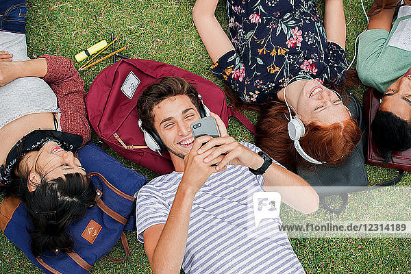 Group of college students relaxing together on grass between classes