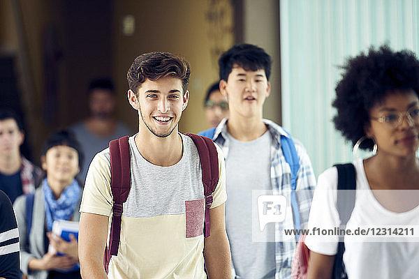 Student smiling as he walks between classes