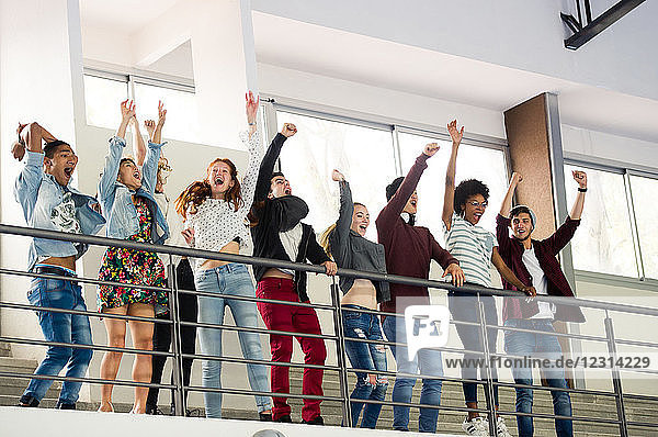 Group of students cheering while watching sports event at school