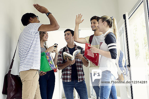 Students giving each other a high-five in corridor