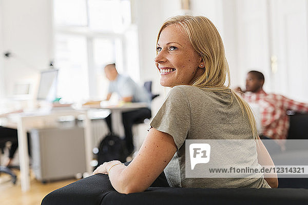 Smiling woman sitting on sofa in office