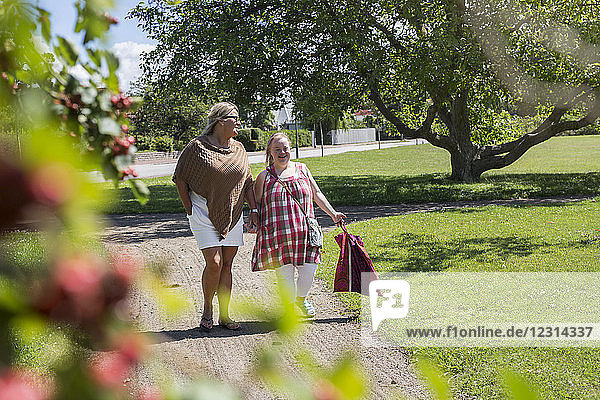Mother and daughter with down syndrome walking in park