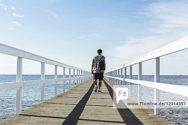Rear view of young man walking on pier