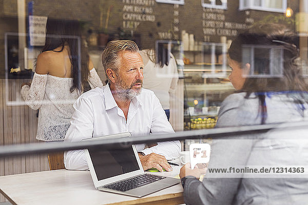 Senior man and mature woman talking in cafe Senior man and mature woman talking in cafe