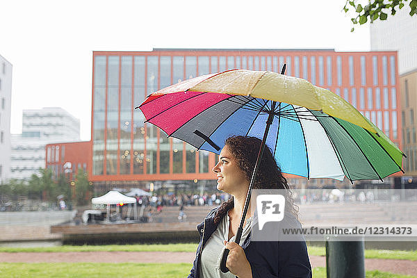 Woman standing under colorful umbrella  concert in background
