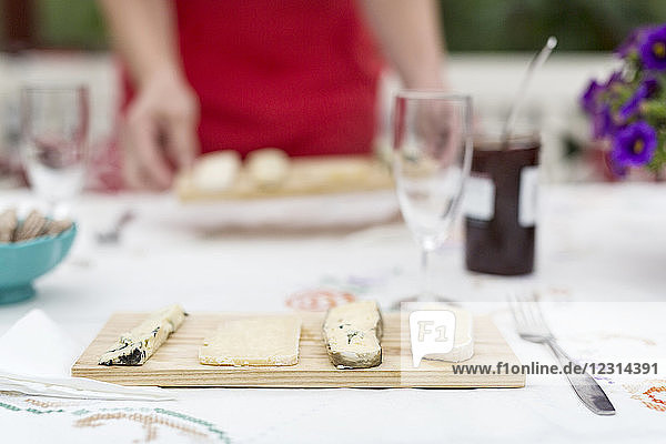 Table with fresh cheese on wooden cutting board