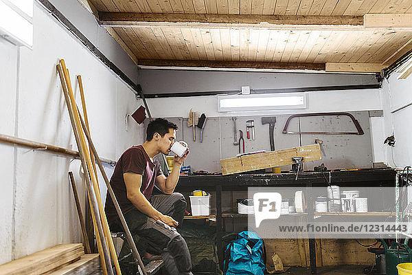 Man drinking coffee in garage