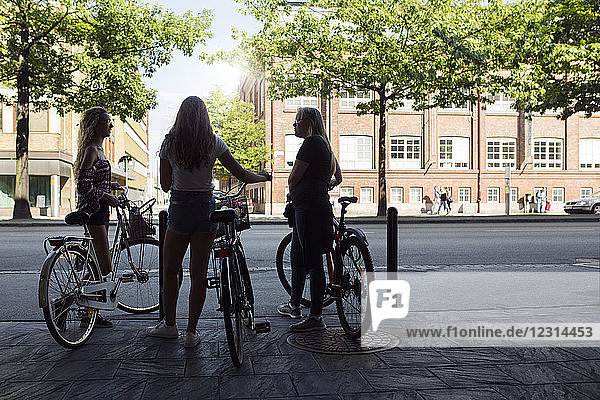 Three teenage girls (14-15) on bicycles talking