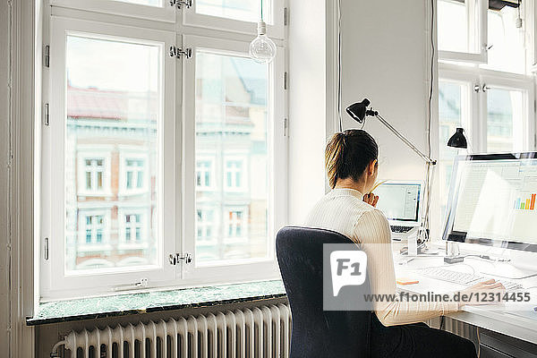 Female editor using computer in office