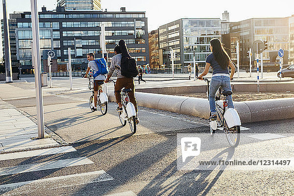 Three people cycling on city street