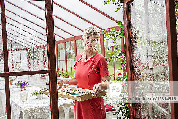 Portrait of woman in conservatory holding wooden tray