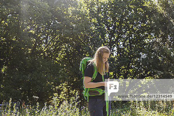 Young woman using phone in meadow