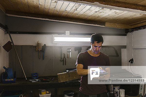 Man using digital tablet in garage