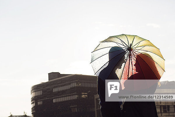 Mid adult couple standing under colorful umbrella at sunset