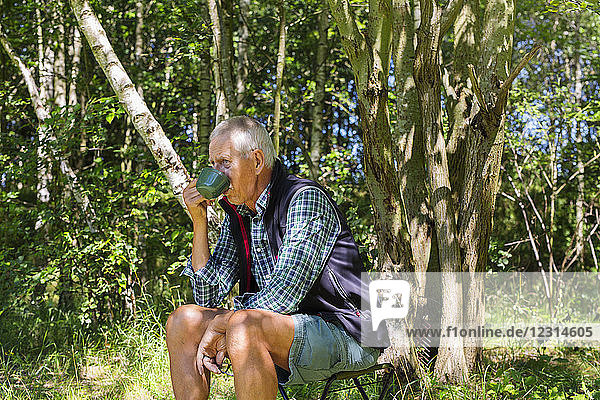 Man drinking from cup in forest Man drinking from cup in forest