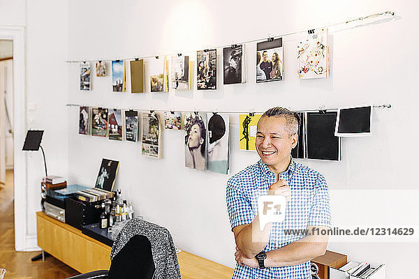 Smiling editor against wall with magazine covers Smiling editor against wall with magazine covers